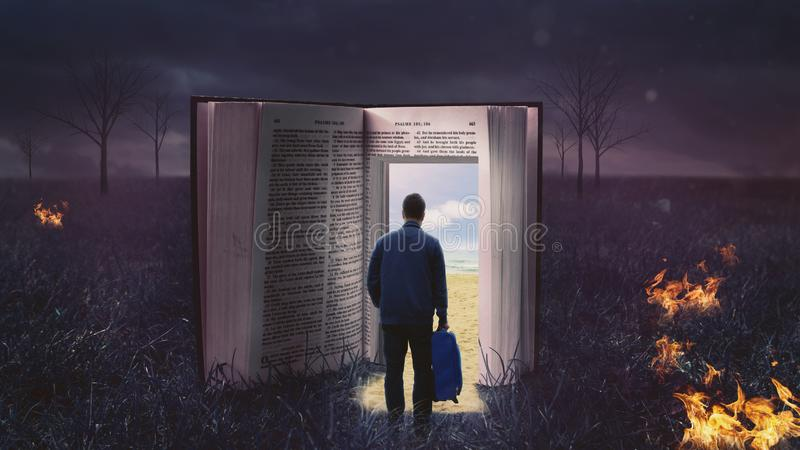 Man walking through open bible. Lonely man with suitcase walking through open bible book to a sunny beach landscape royalty free stock photography