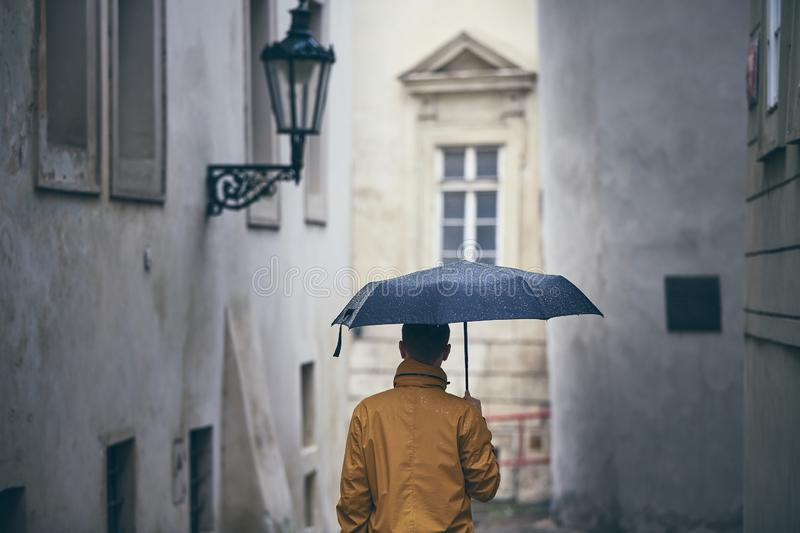 Lonely man with umbrella in rain royalty free stock photography