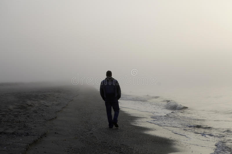 Lonely man walking on a beach stock image