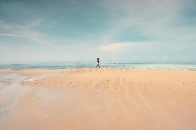 A lonely man walking on the beach. royalty free stock image