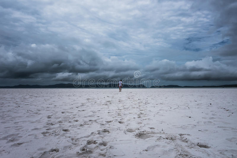 Lonely man walking on the beach stock photo