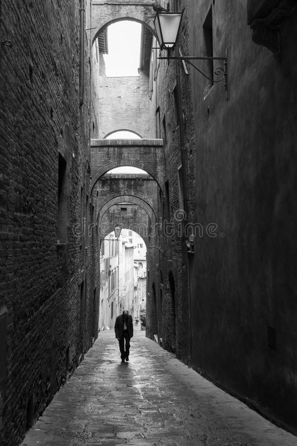 Lonely man walking down the alleys of Siena. stock photography