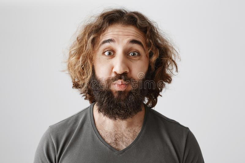 Lonely man wants romance. Studio shot of funny mature eastern male coworker with curly hair puckering, wanting to have stock photography