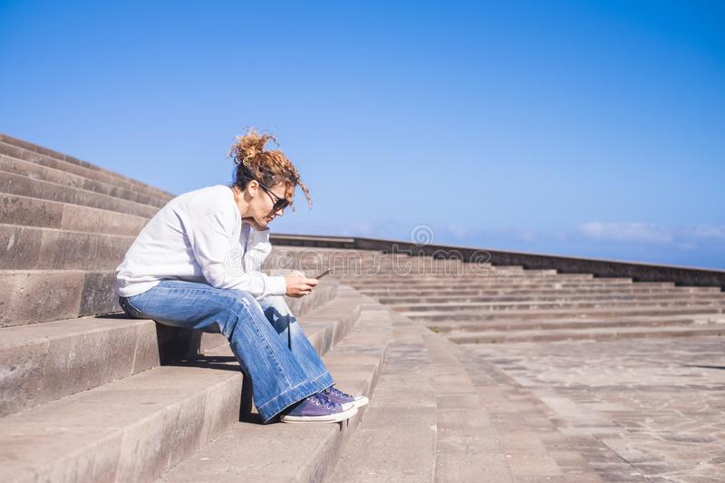 Lonely middle age woman at work with a smartphone sitting on a long beautiful staris in urban contest. leisure with tehnology. Concept for modern lady connected royalty free stock photo