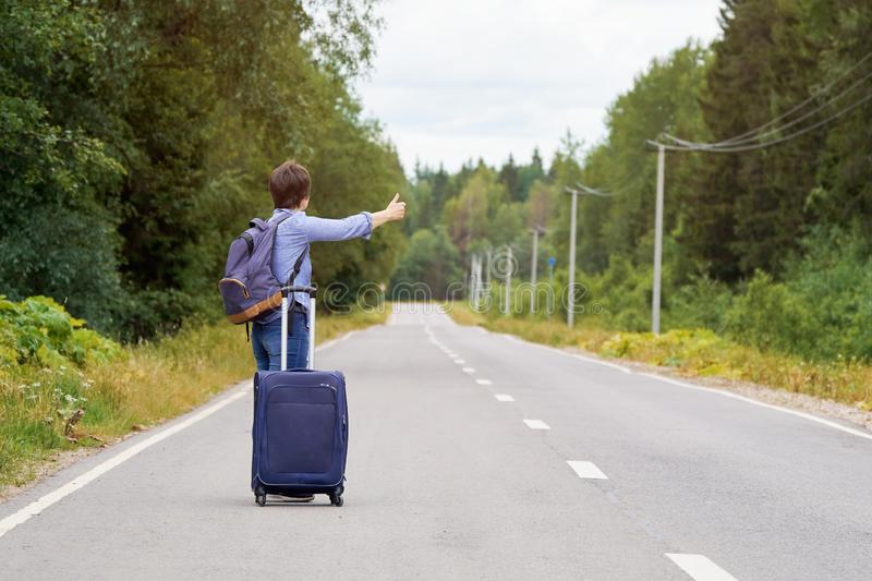 Lonely middle-aged woman with a travel bag hitchhiking on the rural road in summer royalty free stock image