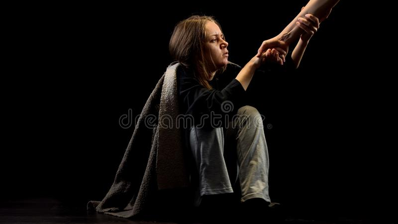 Lonely miserable victim of domestic violence taking helping hand, belief concept. Stock photo stock photos