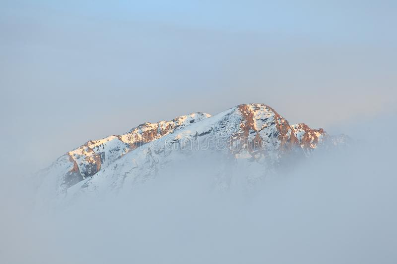 Lonely mountain summit in misty clouds - Himalayas stock image