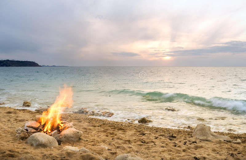 Lonely night fire. On seacoast in the autumn stock photography