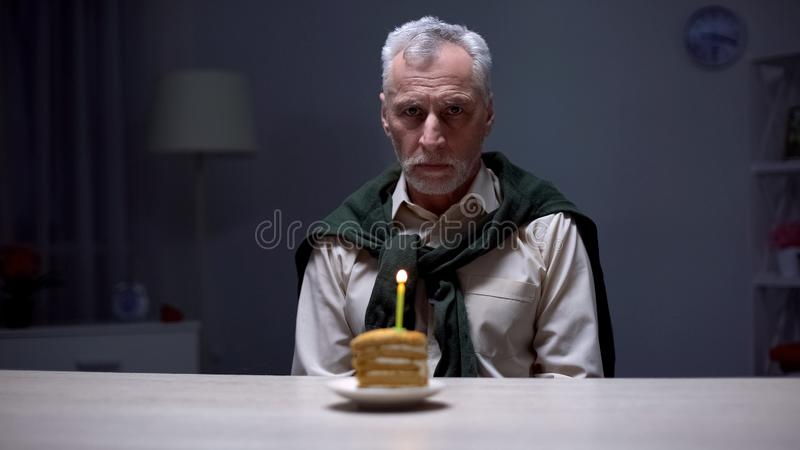 Lonely old man celebrating birthday alone, forgotten by children and relatives royalty free stock image