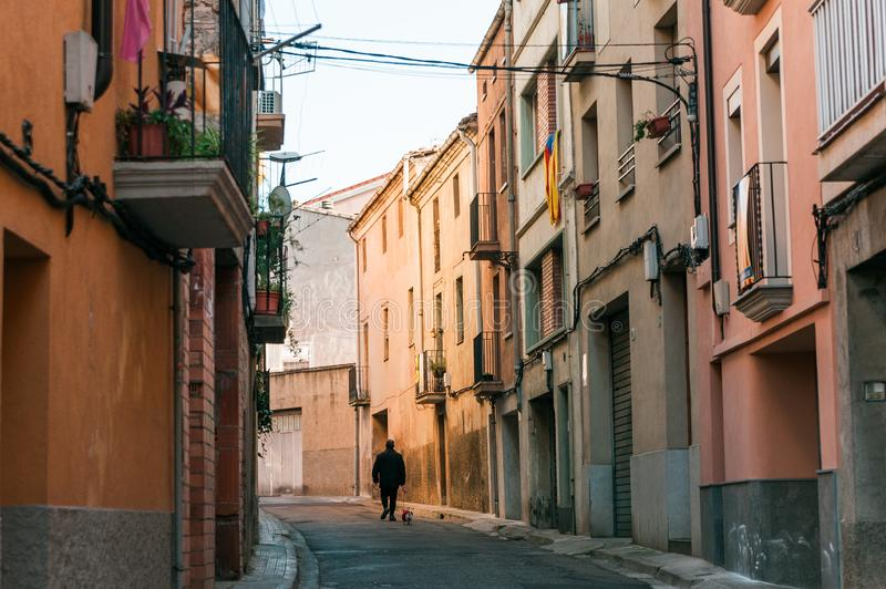 Lonely old man with dog walk in street of small catalan spanish medieval town during sunny spring day. Small town colorful street in spring stock image