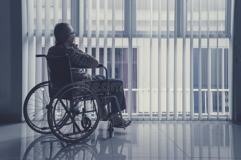 Lonely old man sitting on wheelchair at home royalty free stock photos