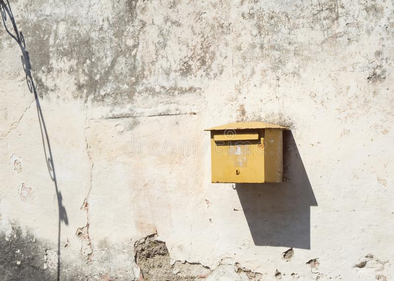 Lonely old postbox with shadow on a shabby wall. Yellow grunge mailbox with sharp shadow hanging on a cracked, shabby stone wall royalty free stock images