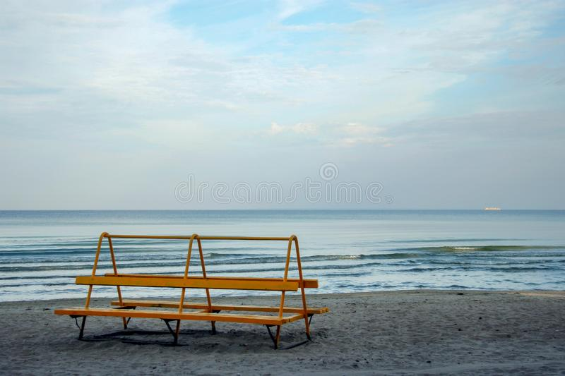 Lonely orange bench on the shore of a calm blue sea with a ship on the horizon. stock photography