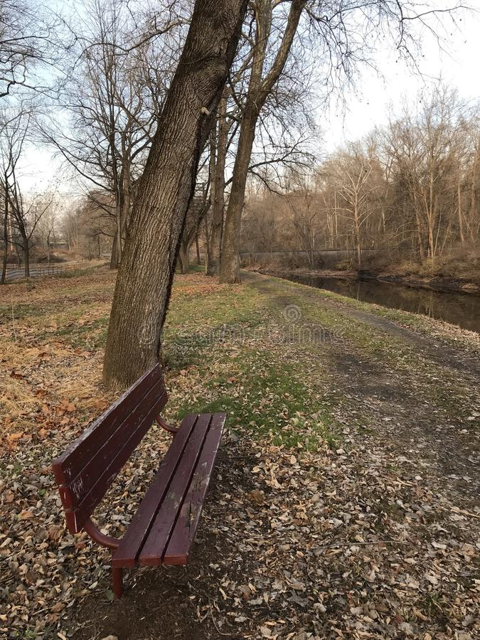 Lonely Park bench by the river. Quiet scenery overlooking the late autumn canal park near Easton Pennsylvania USA. Perfect quiet serene place to take a short royalty free stock photo