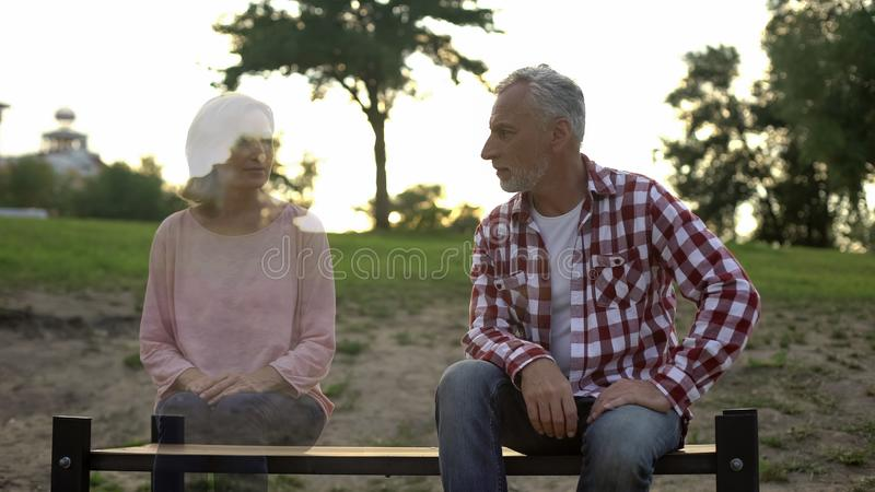 Lonely pensioner sitting on bench, wife appearing beside, loss sorrow, memories. Stock photo royalty free stock photos