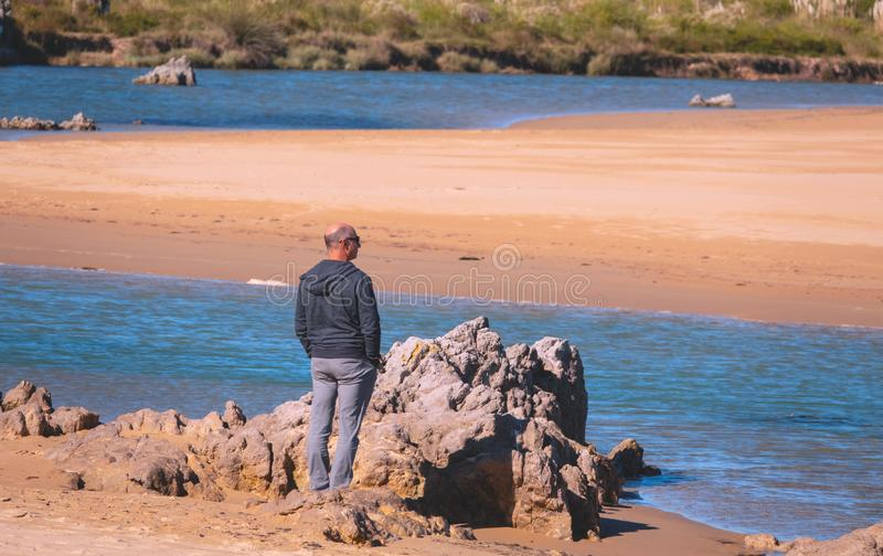 A lonely pensive man stands in silence in the coast of sea royalty free stock images