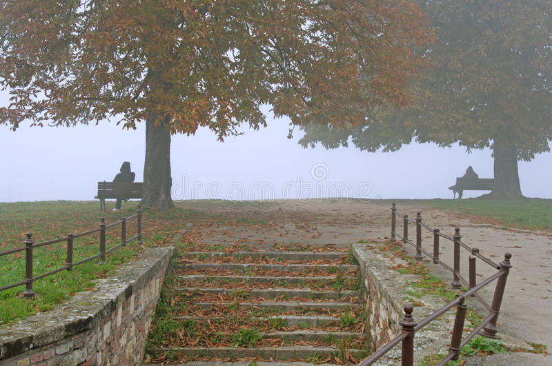 Lonely people in the autumn morning fog. Two lonely people in autumn morning mist sitting on the benches in Kalemegdan Park in Belgrade. The park is located in royalty free stock photography
