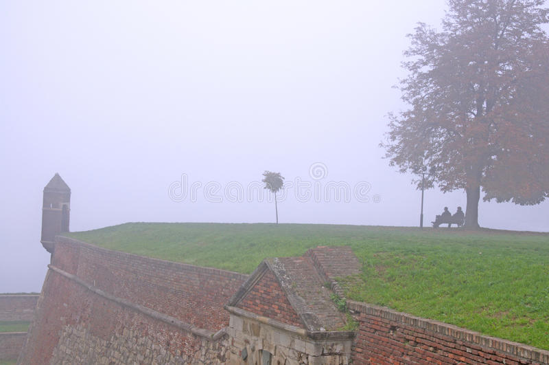 Lonely people in the autumn morning fog. Two lonely people in autumn morning mist sitting on the benches in Kalemegdan Park in Belgrade. The park is located in royalty free stock photo