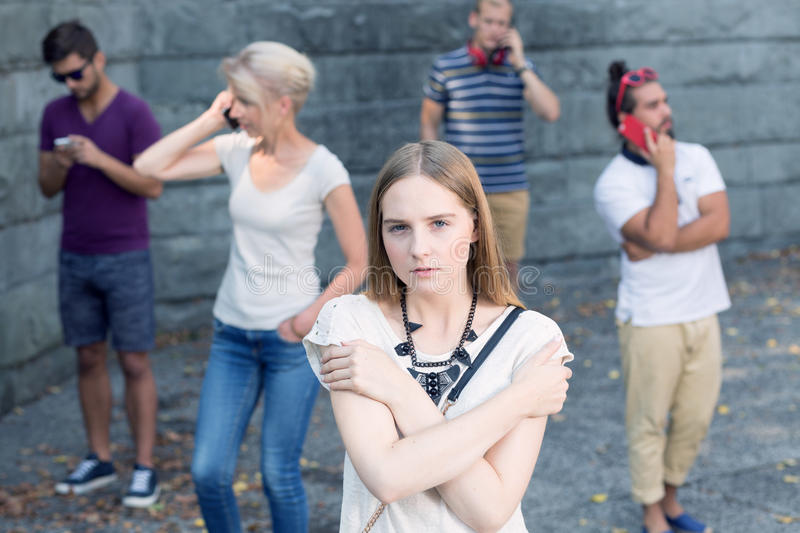 Lonely among people. Pretty young girl lonely among people busy with mobile phones royalty free stock photo