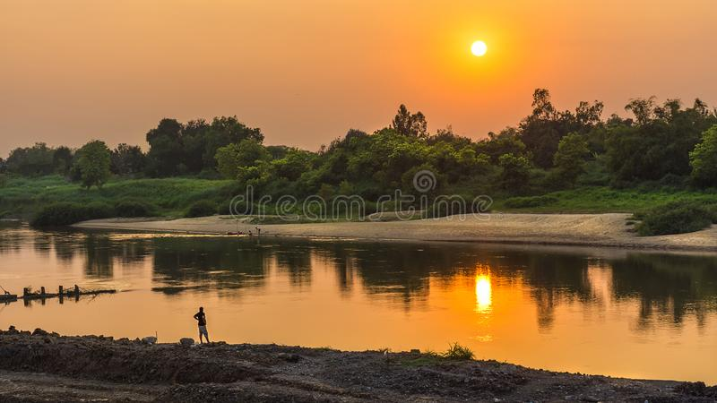 Lonely people watching the sunset. At the river alone royalty free stock photography