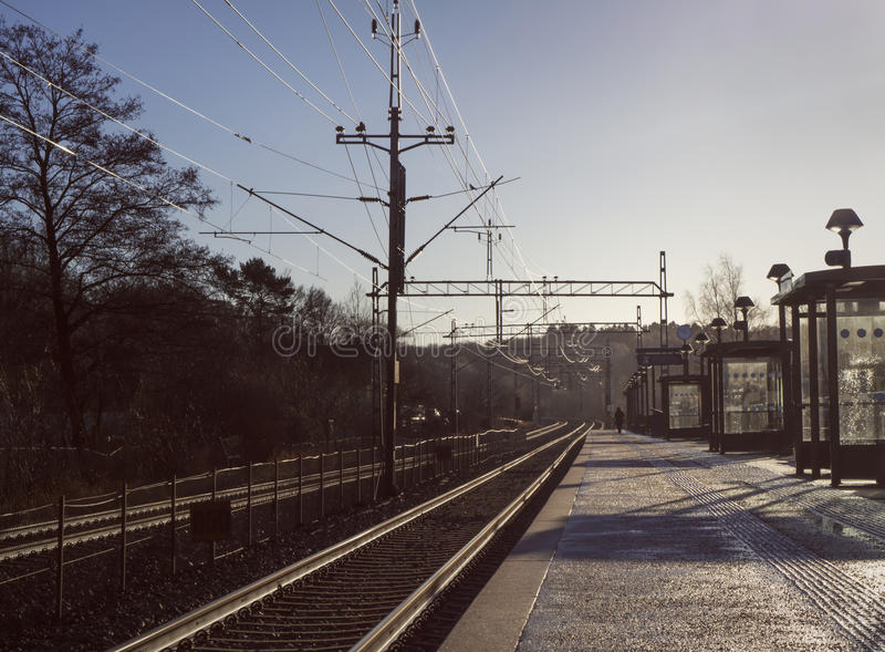 Lonely person on commuter train station a cold, winter morning. Deep perspective of a single person walking along the tracks of a commuter train station on a royalty free stock photos