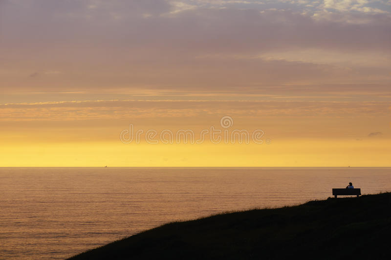 Lonely person contemplating sunset stock photo