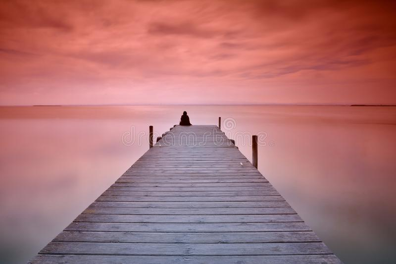 Lonely person sitting on pier. Unrecognizable person sitting on edge of wooden pier at sunset of red and violet colors royalty free stock photos