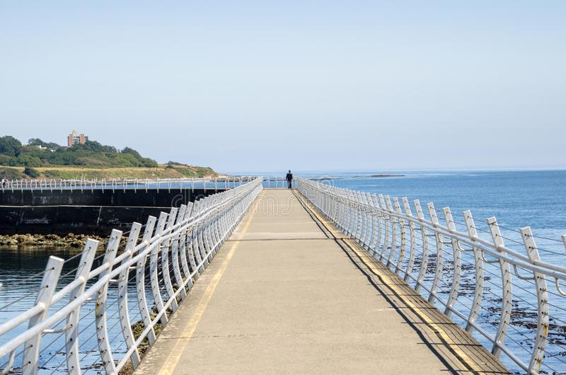 Lonely Person Waking along the Walkway on the Top of Breakwater stock photos