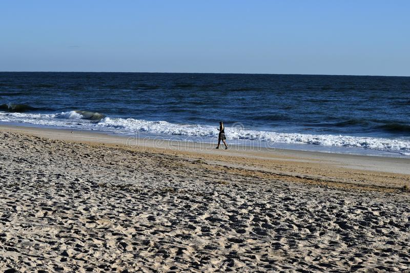 Lonely person walking along beach with surf stock image