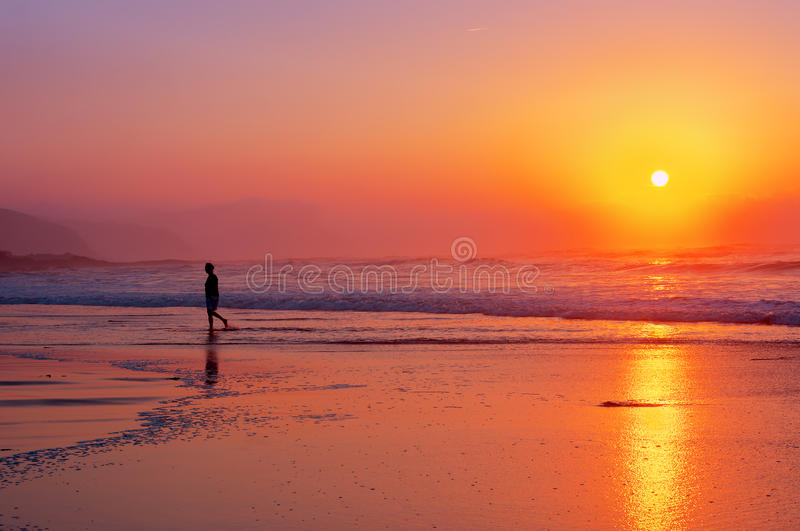 Lonely person walking on beach at sunset royalty free stock photos