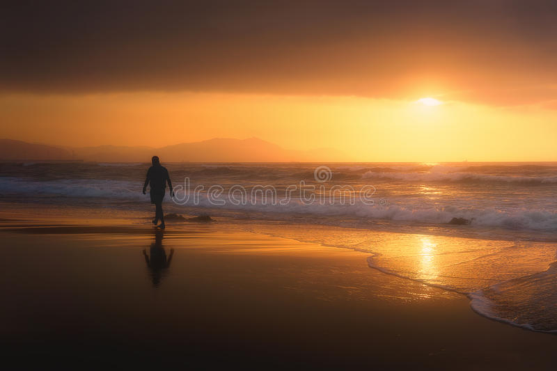 Lonely person walking on beach at sunset stock image