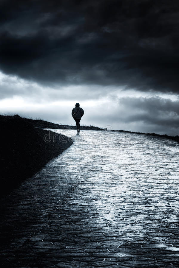 Lonely person walking royalty free stock image