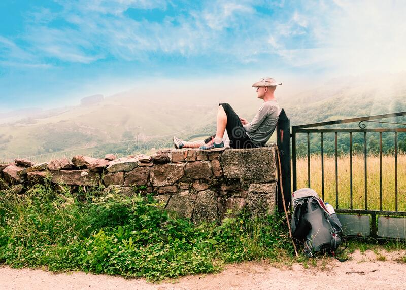 Lonely Pilgrim with backpack resting. Camino de Santiago, Camino del Norte or the Coastal Saint James Way, pilgrimage route along. The Northern coast of Spain stock photography