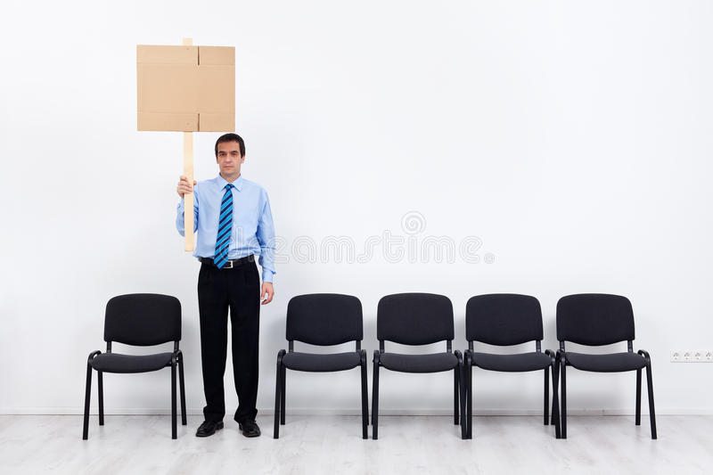 Lonely protesting businessman or employee holding placard. Businessman protesting alone with a placard - fighting for lost causes concept stock images