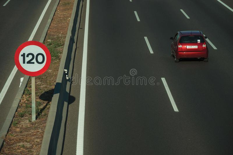 Lonely red car on highway and SPEED LIMIT sign in Madrid stock photos