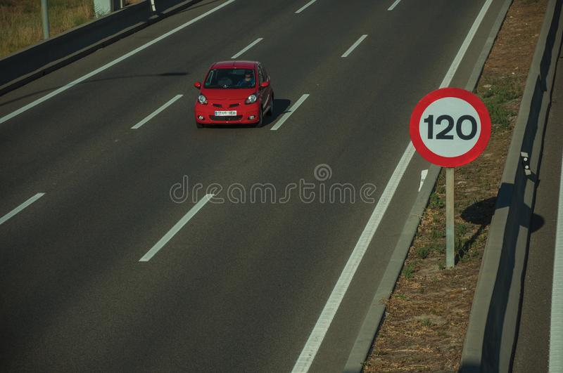 Lonely red car on highway and SPEED LIMIT signpost in Madrid. Lonely red car passing through multi lane highway and SPEED LIMIT signpost, on sunset in Madrid stock photography