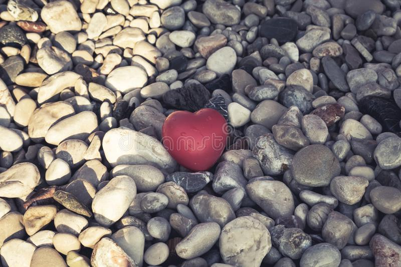 Lonely red heart with drops of water lies on a stone beach, concept of loneliness, concept of love. Symbol of love and family. stock photography