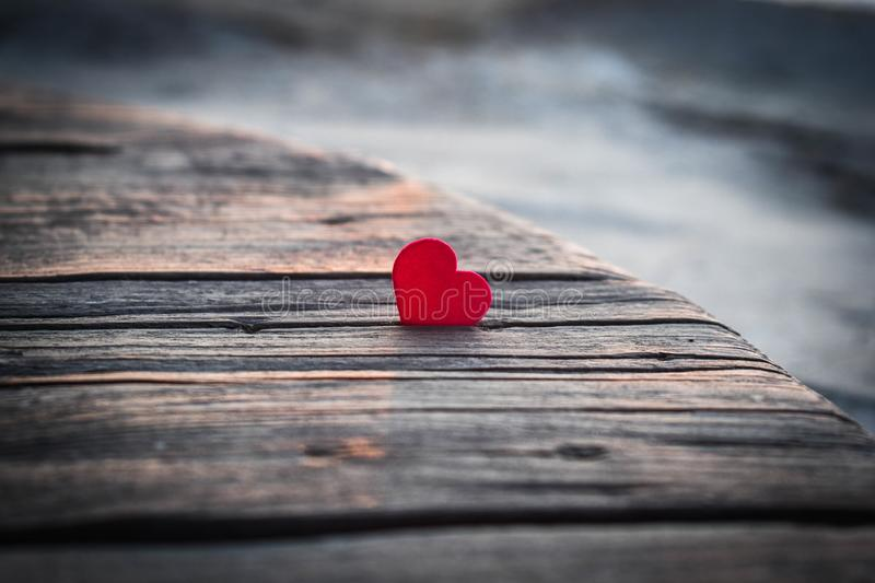 Lonely red heart on a table of old wood stock photo