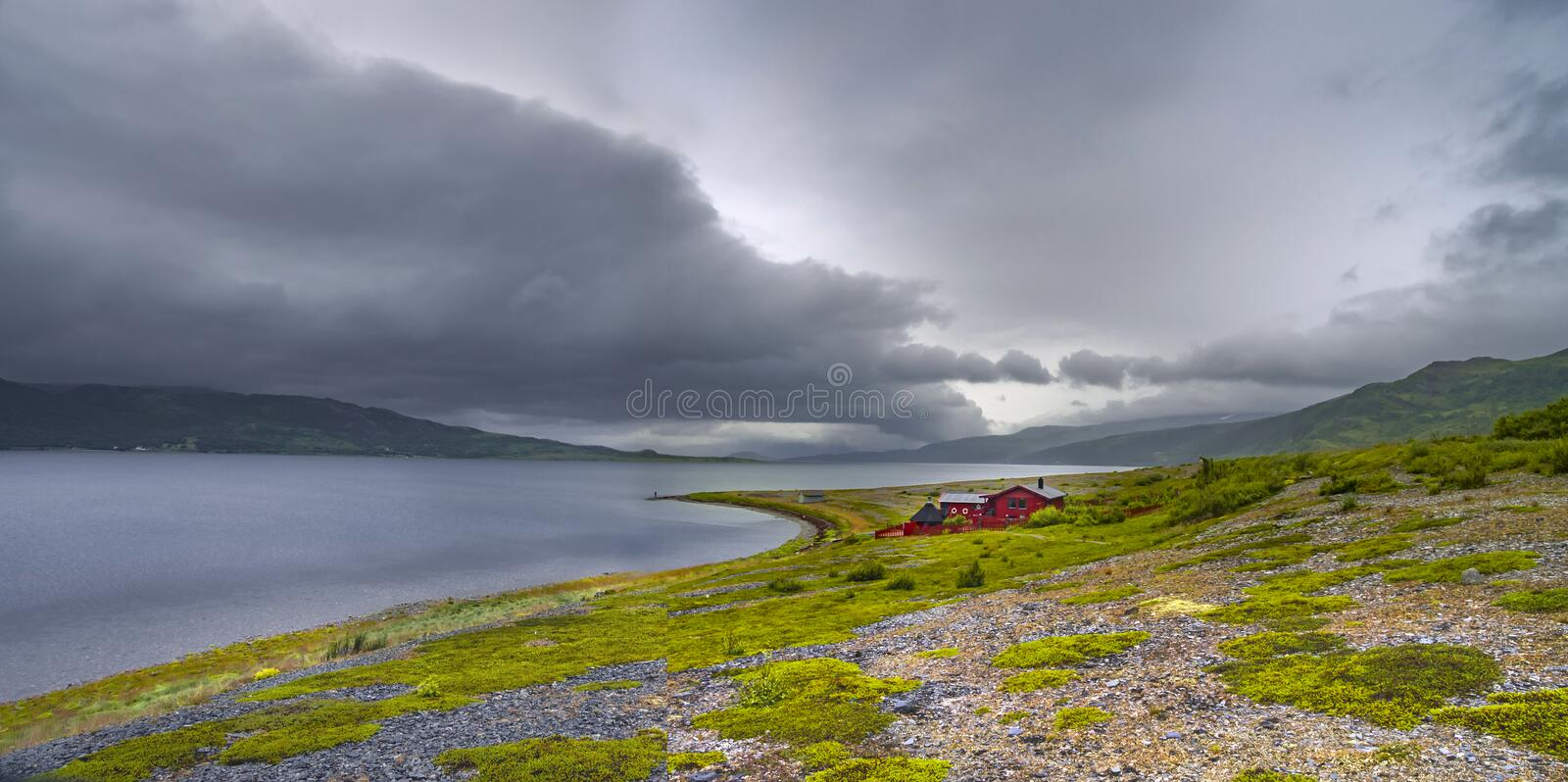 Lonely red house at lake shore in the mountains royalty free stock images