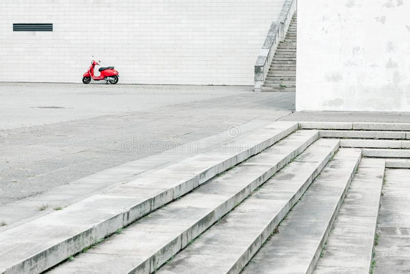 Lonely red scooter against white wall in urban environment stock photos