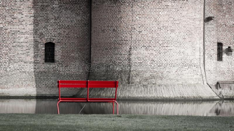 Lonely red wooden bench against a brick wall of old castle building and moat. Outdoor seat sit furniture outside rest street sidewalk background empty park royalty free stock photography