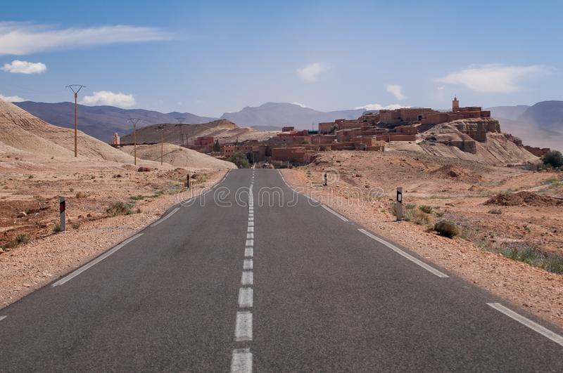 Lonely road to a small village in the desert of Morocco. Straight lonely asphalt road with no traffic with small village in the Moroccan desert royalty free stock photography