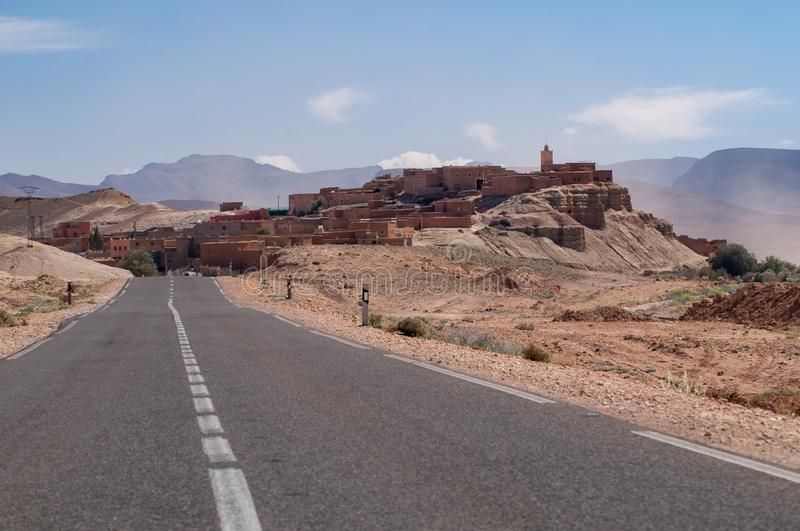 Lonely road to a small village in the desert of Morocco. Straight lonely asphalt road with no traffic with small village in the Moroccan desert stock photo