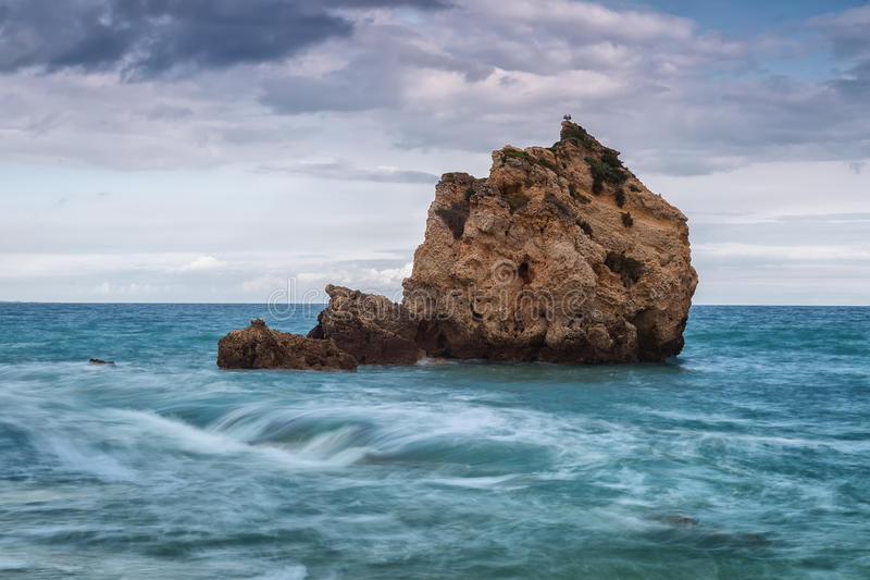 Lonely rock in the sea. Birds rest on the mountain. stock photo