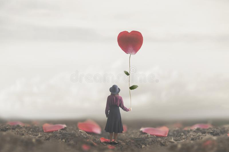 Lonely romantic woman holds a giant petal made to heart royalty free stock photos