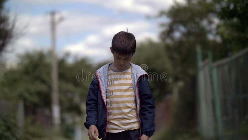 Lonely sad boy walking along the village road with head down, ruffian naughty boy royalty free stock photos