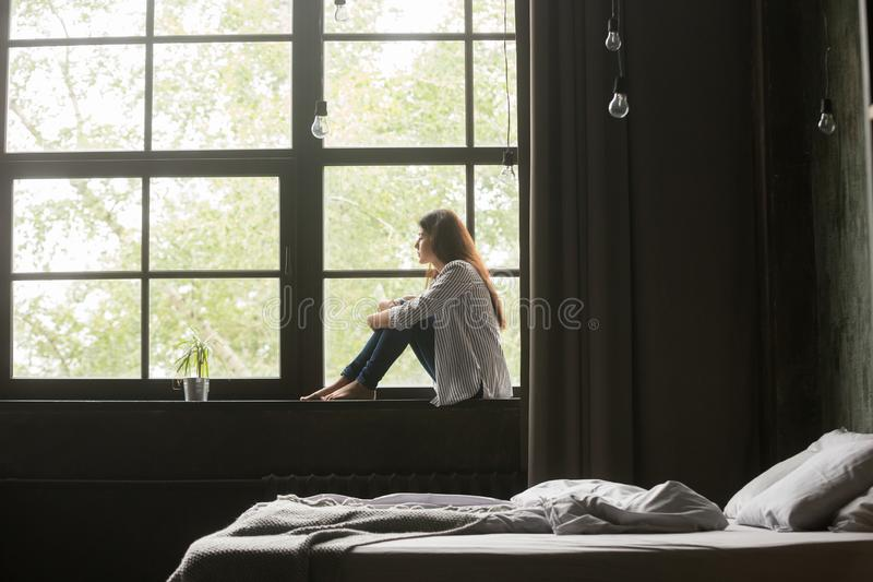 Lonely sad young woman sitting on windowsill at home. Lonely sad brunette female in casual clothes sitting on window sill barefoot and looking at window at home royalty free stock photo