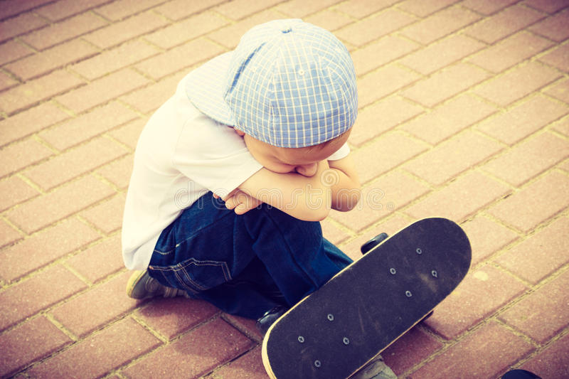 Lonely sad child with skateboard. Loneliness. Lonely sad child boy with skateboard. Depressed sullen kid. Loneliness, solitude and rejection concept stock image