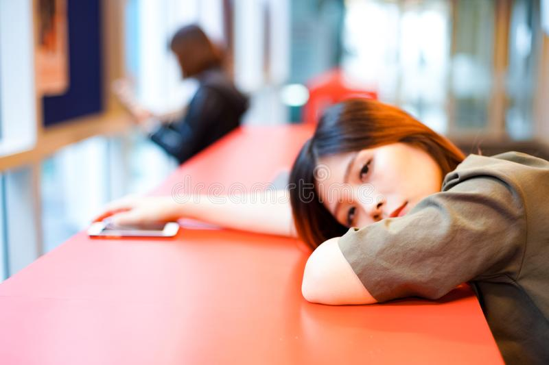 Lonely sad girl looking at nowhere on lying on the table. Lonely sad girl looking at nowhere on lying on the red table adult alone asian attractive beautiful royalty free stock photo