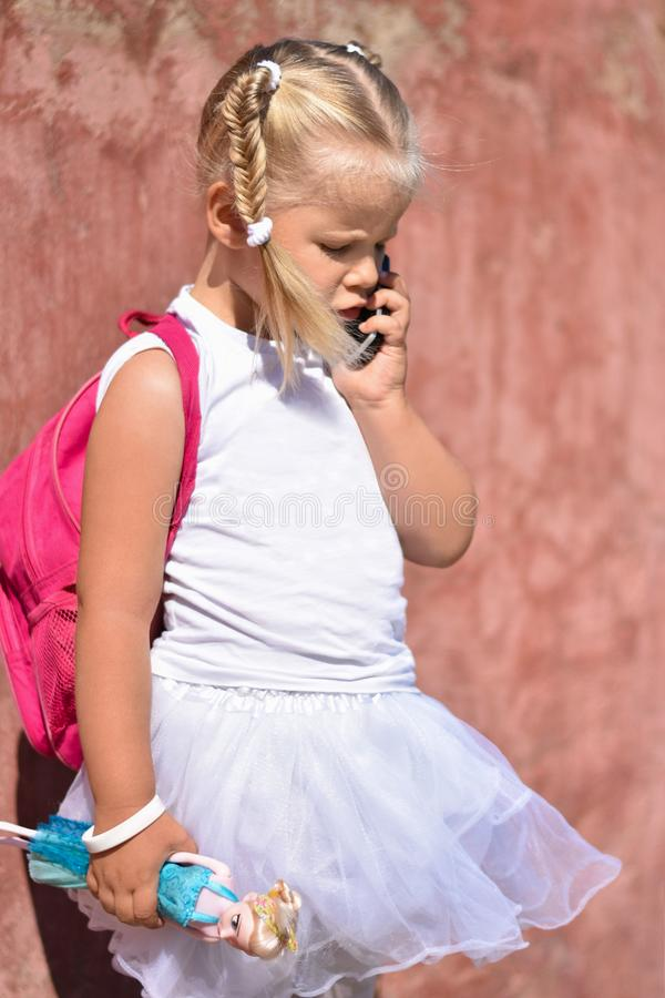 A lonely sad little girl with a backpack and toy in her hand near an old wall in the street was lost and calling on mobile phone stock photo
